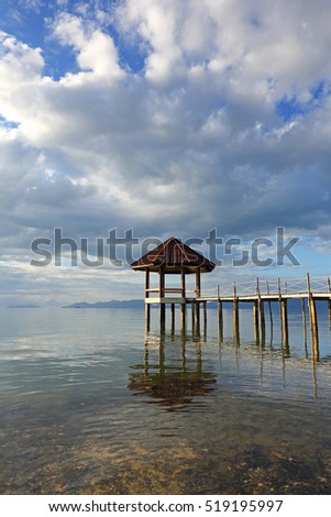Beautiful water reflection, wood landing with clouds at sunrise with pavilion in the sea at Black Sand Beach, Trat