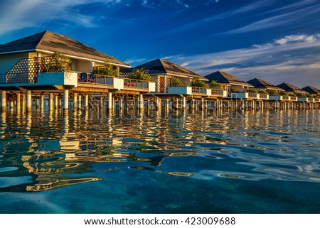 Beautiful water villas on the vibrant blue tropical sea during sunset - stock photo