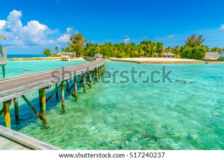 Beautiful water villas with couple snorkeling  in tropical Maldives island