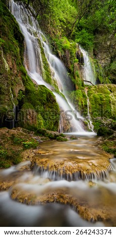 Beautiful waterfall among cliffs in spring time - stock photo
