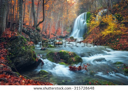 Beautiful waterfall in autumn forest in crimean mountains at sunset. Silver Stream Waterfall in Grand Canyon Of Crimea. - stock photo