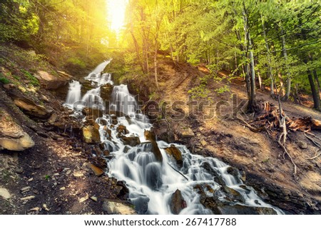 Beautiful waterfall in spring forest. Sunset (Ukraine) - stock photo