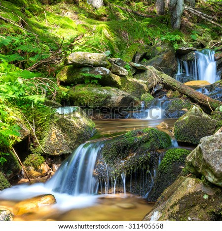 Beautiful waterfall in the green forest. Cascade of motion water - stock photo
