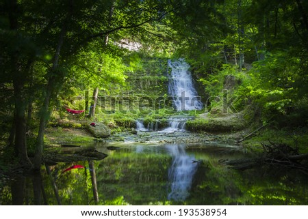 Beautiful waterfall in the woods with a red hammock between two trees onshore.  - stock photo