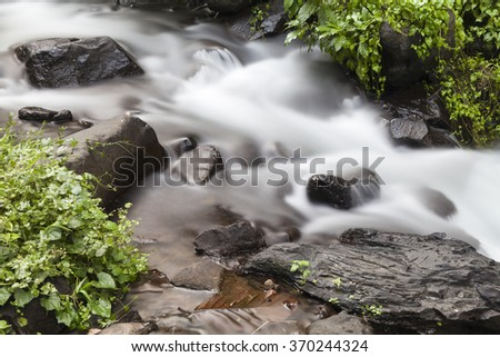 Beautiful waterfall in tropical forest in Bali, Indonesia with slow shutter speed - stock photo