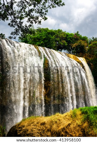 Beautiful waterfall with crystal clear water among green woods on blue sky background in Vietnam. Scenic summer sunny forest landscape. The Elephant waterfall is a popular tourist destination of Asia. - stock photo
