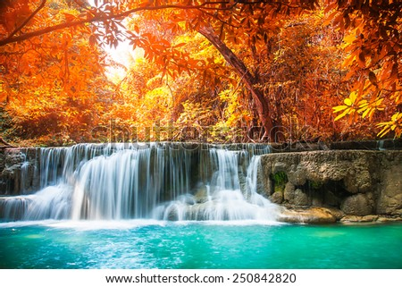 beautiful waterfall with day noon light in autumn forest - stock photo