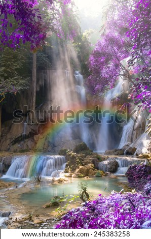 Beautiful waterfall with soft focus and rainbow in the forest - stock photo
