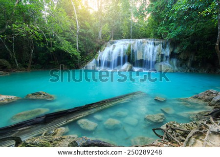 Beautiful waterfall with sunlight rays in deep forest, Erawan National Park in Kanchanaburi, Thailand