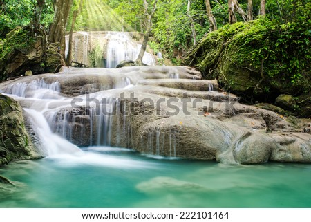 Beautiful waterfall with sunshine in tropical forest, Erawan waterfall, Thailand   - stock photo