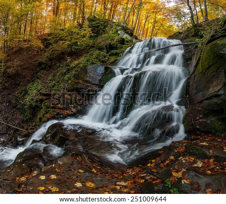 Beautiful waterfall with white jets, surrounded by golden autumn forest - stock photo