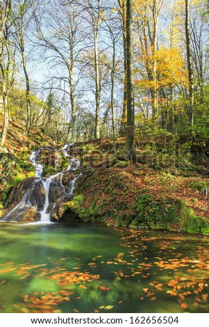 Beautiful waterfalls in the forest on a sunny autumn day in the mountains