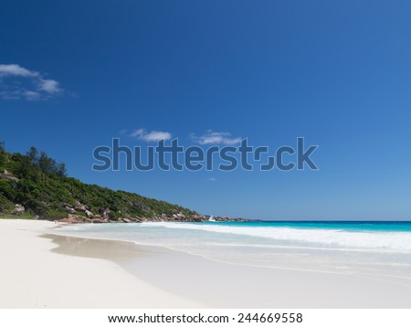 beautiful waves breaking on the sea shore in the Seychelles beach with white sand and clear blue sky with light clouds - stock photo
