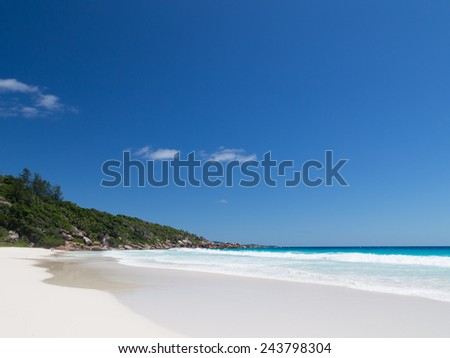 beautiful waves breaking on the sea shore in the Seychelles beach with white sand and clear blue sky - stock photo