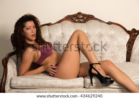 Beautiful wavy haired multiracial woman in purple lingerie