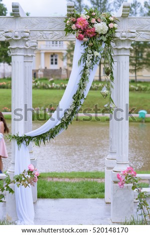 Beautiful wedding arch for marriage decorated with lace fabric and flowers. White decor for bride and groom. Colorful decoration for celebration. Beauty bridal interior