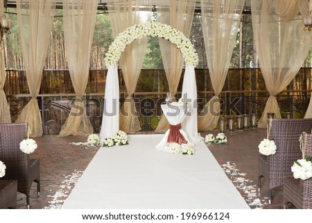 Beautiful wedding arch with white roses in the restaurant - stock photo