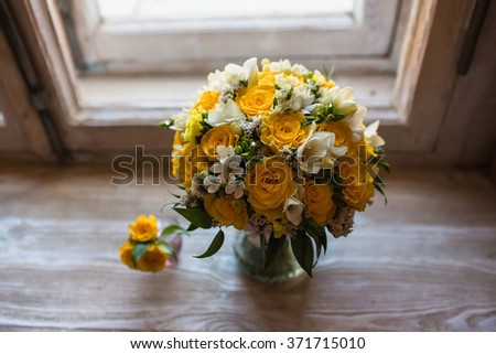 Beautiful wedding bouquet and groom's boutonniere on the windowsill background