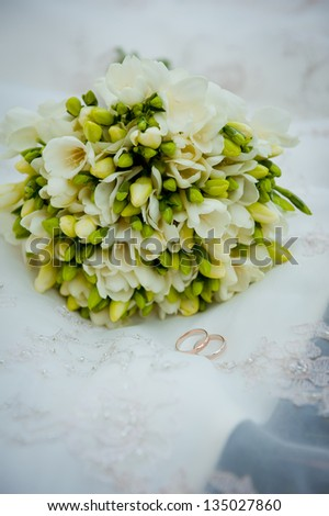 beautiful wedding bouquet and rings lying on the bridal veil - stock photo