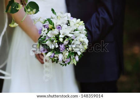 beautiful wedding bouquet at bride's hands - stock photo