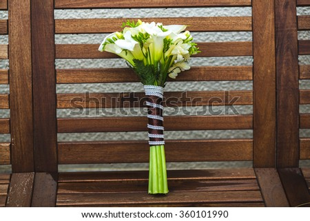 Beautiful wedding bouquet at the brown wooden background