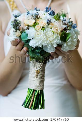 Beautiful wedding bouquet in bride's hand  (soft focus) - stock photo