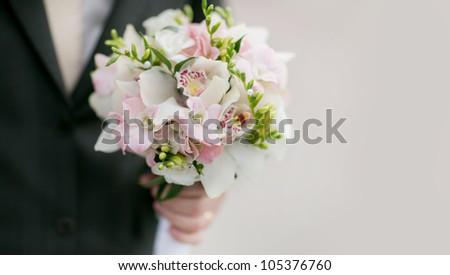 Beautiful wedding bouquet in bridegroom's hand - stock photo