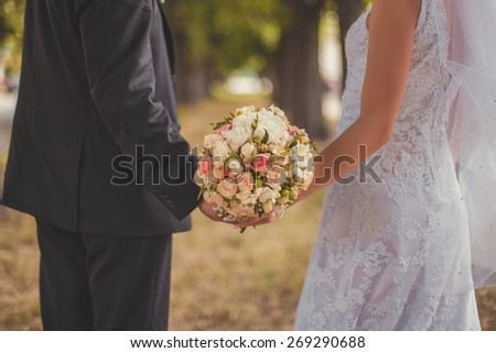 Beautiful wedding bouquet in brides and grooms hands. - stock photo