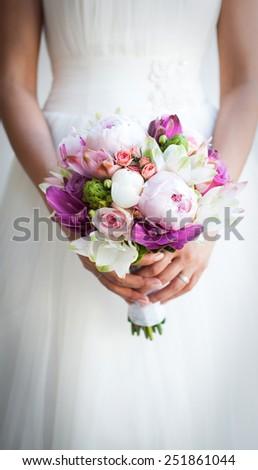 Beautiful wedding bouquet in hands of the bride - stock photo