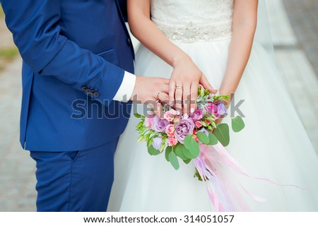 Beautiful wedding bouquet in hands of the bride and groom. Wedding rings.