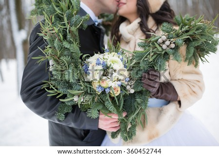 Beautiful wedding bouquet in hands of the bride and groom with spruce scarf in winter