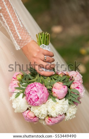 Beautiful wedding bouquet in hands of the bride, focus on hand