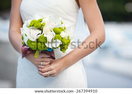 beautiful wedding bouquet of filin green and Cymbidium flowers in hands of the bride - stock photo