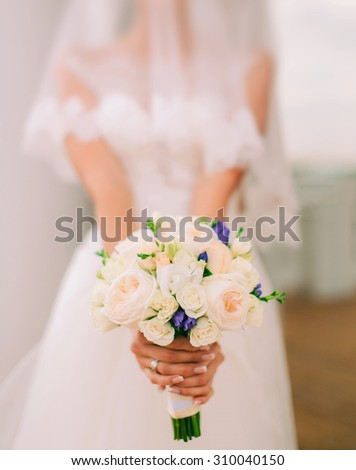 Beautiful wedding bouquet of flowers in hands of the bride - stock photo