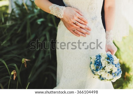 Beautiful wedding bouquet of flowers in hands of the bride and groom