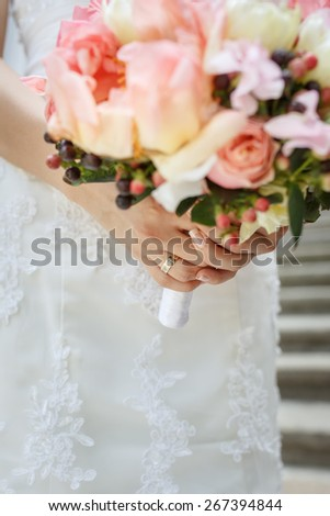 Beautiful wedding bouquet of pink and white peony flowers in hands of the bride - stock photo
