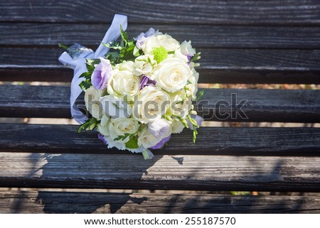 Beautiful wedding bouquet of rose, eustoma and chrysanthemum flowers on on wood boards - stock photo