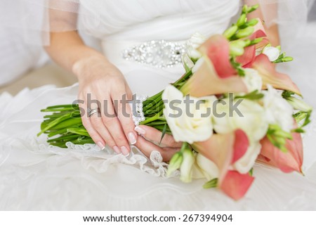 Beautiful wedding bouquet of rose Vendella, calla and freesia flowers in hands of the bride - stock photo
