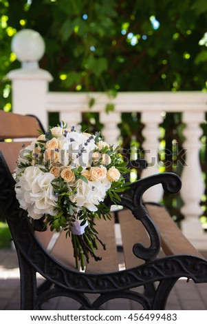 Beautiful wedding bouquet of roses and hydrangeas lying on a wooden bench