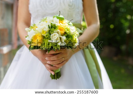 Beautiful wedding bouquet of roses, chrysanthemum and freesia flowers in hands of the bride - stock photo