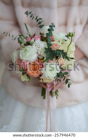 Beautiful wedding bouquet of roses in hands of bride. - stock photo