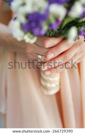 Beautiful wedding bouquet of statice in hands of the bride, manicure - stock photo