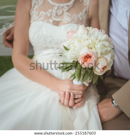 Beautiful wedding bouquet of white and pink  paeonies in hands of the bride