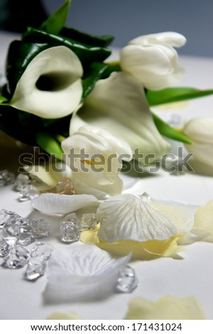 Beautiful wedding bouquet of white callas and tulips lying on the table