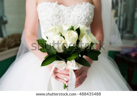 Beautiful wedding bouquet of white roses in bride's hands