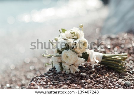 beautiful wedding bouquet of white roses lying on the pebbles on the beach - stock photo