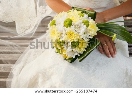 Beautiful wedding bouquet of yellow and green chrysanthemum flowers in hands of the bride - stock photo
