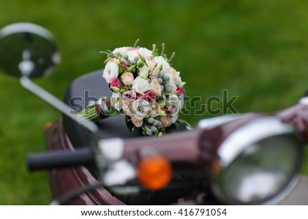 Beautiful wedding bouquet on scooters. Front view. Green lawn in the background - stock photo