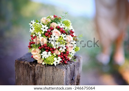 beautiful wedding bouquet with red flowers lying on a tree stump. - stock photo