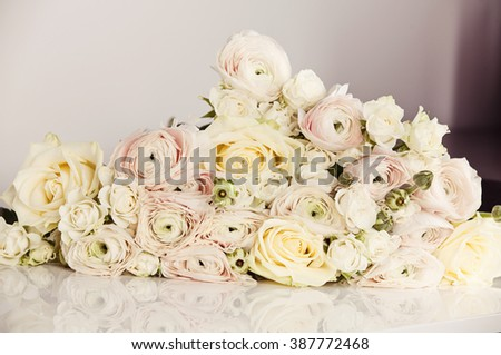 Beautiful wedding bouquet with rose bush, Ranunculus asiaticus as a background. (soft focus) - stock photo